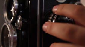 La main de la fille tord la roue de foyer d'une caméra moyenne de format de cru banque de vidéos
