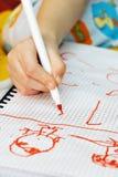 La main de gosses dessine les crayons lecteurs feutres sur le papier Photographie stock