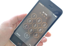 La main de jeune femme tenant l'iPhone 5c d'Apple et préparent entrent le mot de passe Photographie stock libre de droits