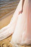 La main de jeunes mariées avec l'anneau de mariage sur le fond de belles longues robes de mariage sur la plage au coucher du sole Photos libres de droits