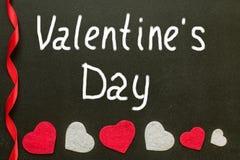 La main de jour du ` s de Valentine écrit sur le panneau de craie Photos libres de droits