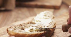 La main de l'adolescence femelle répand le beurre sur la tranche de pain rustique Photos stock