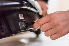 La main de l'adolescence de vue de jour de plan rapproché branchent dedans le câble de remplissage au scooter électrique Photos stock