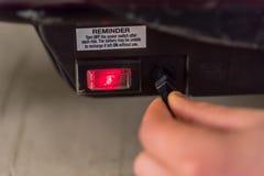 La main de l'adolescence de vue de jour de plan rapproché branchent dedans le câble de remplissage au scooter électrique Image libre de droits