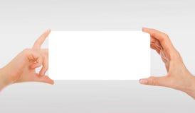 La main de l'adulte et la main de l'enfant tenant le livre blanc, carton Photographie stock