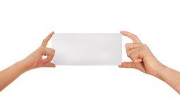 La main de l'adulte et la main de l'enfant tenant le livre blanc, carton Fond blanc avec l'espace pour le texte Photo stock
