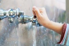 La main de l'enfant avec de l'eau l'eau du robinet Image libre de droits