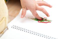 La main de l'enfant avec les peintures colorées de doigt Image libre de droits