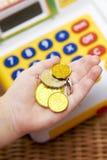 La main de l'enfant avec les pièces de monnaie et la caisse comptable de jouet image stock