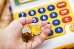 La main de l'enfant avec les pièces de monnaie et la caisse comptable de jouet photo stock
