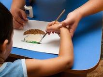 La main de l'enfant avec une brosse pour le dessin Image libre de droits
