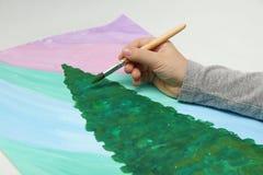 La main de l'enfant dessine un arbre de Noël image stock