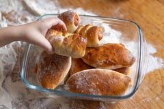 La main de l'enfant a pris un petit pain hors d'un plat sur une table en bois couverte de la farine images stock