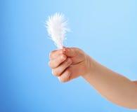 La main de l'enfant retenant la clavette blanche image stock