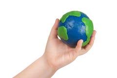 La main de l'enfant retenant un globe Images libres de droits