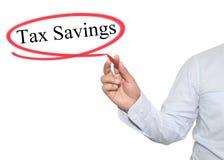 La main de l'homme écrivent l'épargne d'impôts des textes avec la couleur noire d'isolement dessus Photo libre de droits