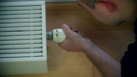 La main de l'homme ajustant la température de radiateur banque de vidéos