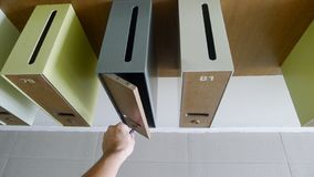 La main de l'homme avec la clé ouvrant une boîte de courrier Vue de plan rapproché images stock