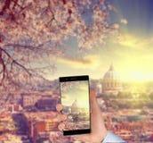 La main de l'homme avec le téléphone intelligent prenant une photo devant la cathédrale de St Peter à Rome, Italie Photographie stock