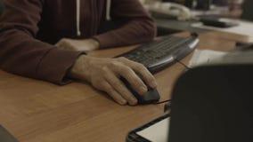 La main de l'homme déplace le foyer de souris d'ordinateur dedans sur une table en bois banque de vidéos