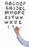 La main de l'homme d'affaires écrivent des lettres d'alphabet dessus Photos libres de droits
