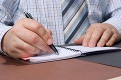 La main de l'homme d'affaires avec une écriture de crayon lecteur quelque chose. Photographie stock libre de droits