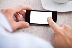 La main de l'homme d'affaires tenant le smartphone avec l'écran vide Images stock