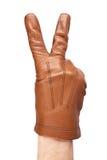 La main de l'homme dans les gants montrant un signe de victoire Photo stock