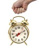 La main de l'homme dans un poing environ pour frapper une horloge rouge Images stock