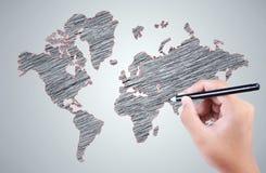 La main de l'homme dessinant une carte du monde au-dessus du gris Photos libres de droits