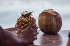 La main de l'homme dominicain tenant un cocktail de colada de pina a servi dans l'ananas, dans une plage tropicale en R?publique  images libres de droits