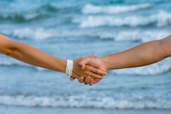 La main de l'homme et du femme dans l'amour sur l'océan Images libres de droits