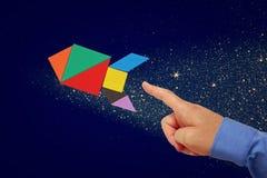 La main de l'homme se dirigeant à la fusée faite à partir du puzzle de tangram Images stock