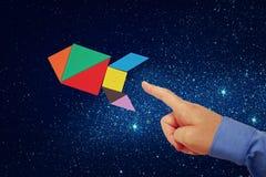 La main de l'homme se dirigeant à la fusée faite à partir du puzzle de tangram Image stock
