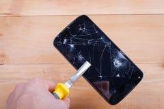 La main de l'homme, serrée par le téléphone portable de pinces avec un écran cassé Images libres de droits