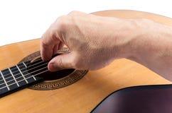 La main de l'homme sur des ficelles de guitare classique sur le blanc Photographie stock libre de droits