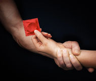 La main de l'homme tenant la main de femme avec un préservatif Image libre de droits