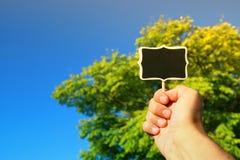 La main de l'homme tenant le signe en bois vide Images libres de droits