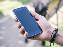 La main de l'homme tenant le smartphone mobile photographie stock