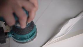 La main de l'homme tient le polisseur vert électronique et travaille à la surface blanche clips vidéos
