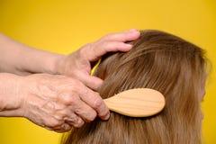 La main de la femme agée peignant les cheveux de la petite-fille Photo libre de droits