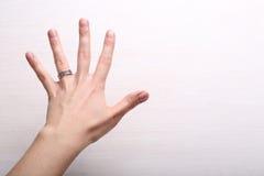 La main de la femme avec l'anneau sur le fond clair Images stock