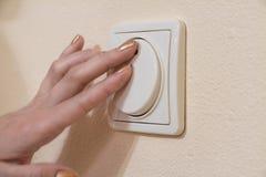 La main de la femme avec le doigt sur l'interrupteur de lampe Image libre de droits