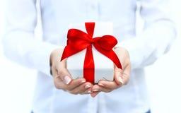 La main de la femme avec un petit boîte-cadeau blanc avec l'arc Images stock