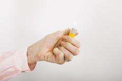 La main de la femme d'affaires tenant l'allumeur de cigarette avec la flamme dans le bureau Image stock