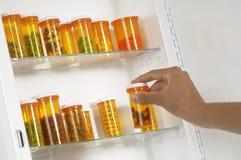 La main de la femme prenant la bouteille de pilule de l'étagère Photo libre de droits