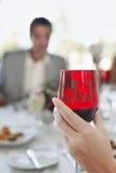 La main de la femme tenant le verre à vin rouge Photographie stock libre de droits