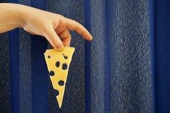 Un morceau de fromage chez la main de la femme Images stock