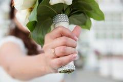 La main de la jeune mariée sur le bouquet de mariage Images stock