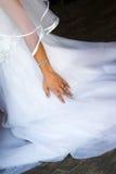 La main de la mariée contre sa robe Photographie stock